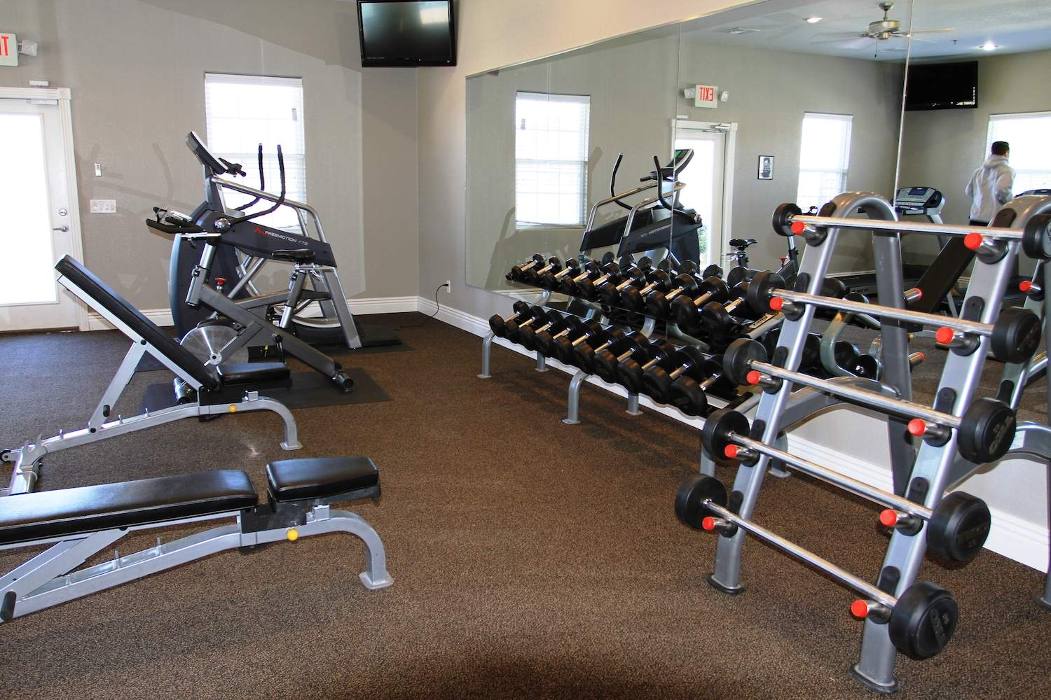 Weights, with elliptical and mirrors in fitness center at Pines at Southridge