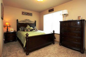 Bedroom with queen set of furniture and bay window. Carpeted floors.