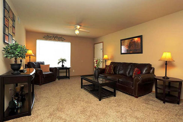 Living room with furniture and bay window in Tahlquah apartment at Pines at Southridge