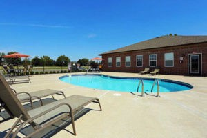Pool at Pines at Southridge Apartments. In ground with plenty of space to relax.