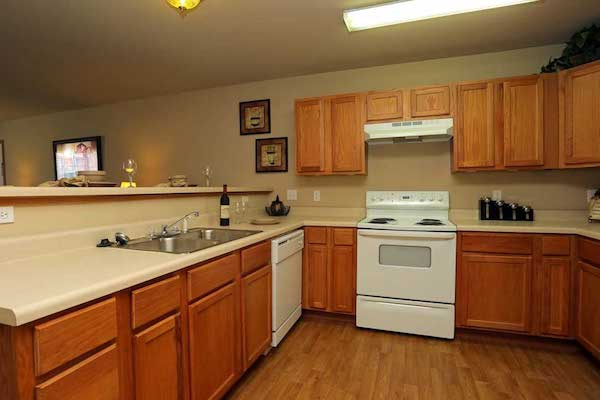 Standard apartment kitchen including oak cabinets, dishwasher, stove, sink and spacious countertops.